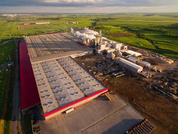 Riesige betonfabrik mit rohren zwischen den feldern. luftaufnahme
