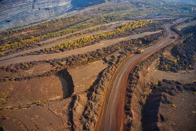 Riesige hügel aus alteisenerz in der nähe des steinbruchs. belaz-lastwagen fahren in bergbaufabrik, minensteinbruch in der ukraine