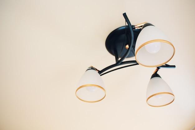 Riesige kronleuchter-nahaufnahme mit glühbirnen auf ausgefallener decke.