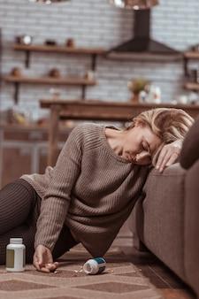 Riesige menge. reife blonde frau schläft ein, nachdem sie eine große menge medikamente eingenommen hat