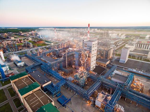 Riesige ölraffinerie mit metallkonstruktionen, rohren und destillation des komplexes mit brennenden lichtern in der abenddämmerung. luftaufnahme