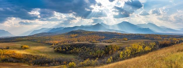 Riesige prärie und wald im schönen herbst. sonnenlicht vorbei an blauem himmel und wolken auf bergen. waterton scenic spot, nationalpark waterton lakes, alberta, kanada.