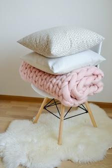 Riesige rosa plaid-decke woolen gestrickt auf weißer hölzerner schemel-stuhl-ausgangsskandinavier-art