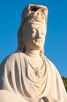 Riesige statue von ryozen kannon bodhisattva avalokitesvara, bekannt für ihr mitgefühl für lebewesen, beleuchtet von erstaunlichem sonnenlicht.