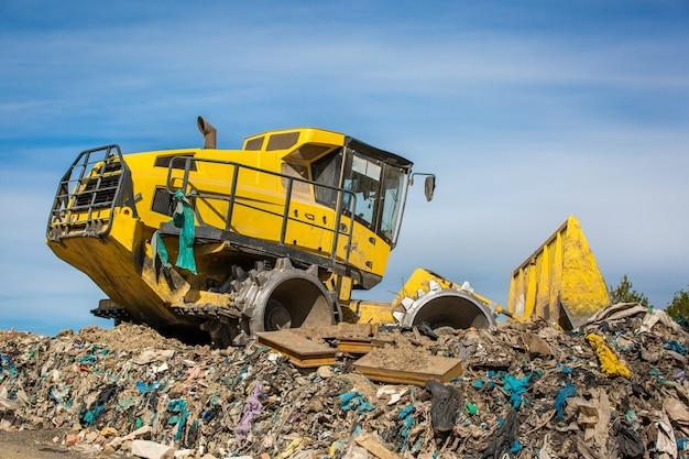 Riesiger bulldozer, der an der riesigen deponie oder müllkippe arbeitet, verschmutzungskonzept