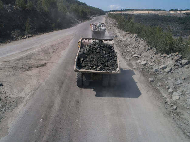 Riesiger industrieller muldenkipper in einem steinbruch, der marmor oder granit transportiert, der von einer drohne auf der straße geschossen wird
