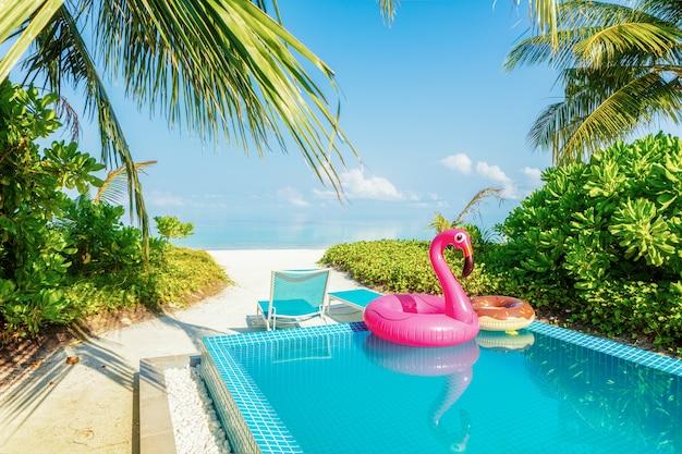 Riesiger rosa aufblasbarer schwan durch blaues poolwasser am tropischen landhaus der laxery. sommerurlaub urlaub