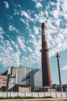 Riesiger schornstein macht wolken im himmel an sonnigem tag. industriegebäude mit großem rohr des braunen ziegels unter blauem himmel. produktionsgebäude im industriegebiet. fabrik hinter zaun mit stacheldraht.