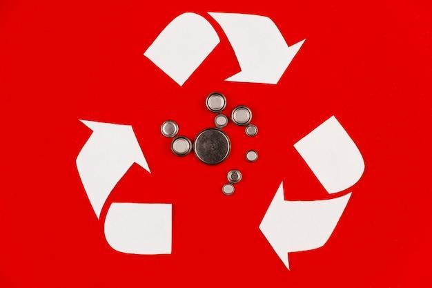 Riesiges weißes recycling-wiederverwendungszeichen-symbol mit alten gebrauchten runden flachen alkalischen lithiumzellenbatterien des kreises