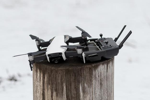 Riga, lettland - 20. märz 2021: weißer quadrocopter dji mavic air mit fernbedienung nach einem flug auf einem holzblock an einem wintertag