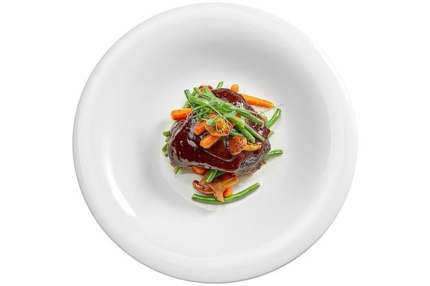Rinderbackensteak, karamellisiert in weinsauce mit pfifferlingen und spargel in einem weißen teller. isoliert auf weißer oberfläche. von oben betrachten