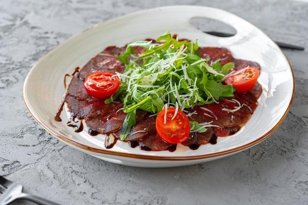 Rindercarpaccio mit rucola und parmesan auf grauer oberfläche