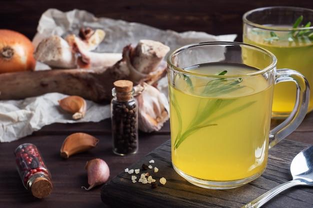 Rinderknochen und gemüsebrühe mit kurkuma-gewürzen in einem glas