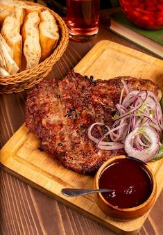 Rindersteak mit grill, bbq-soße und kräutern, zwiebelsalat, gegrilltem pfeffer und tomate auf hölzerner platte