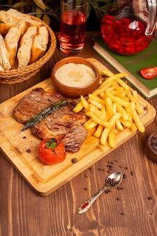 Rindersteak mit pommes-frites, sauerrahmmayonnaisesoße und kräutern auf holzplatte