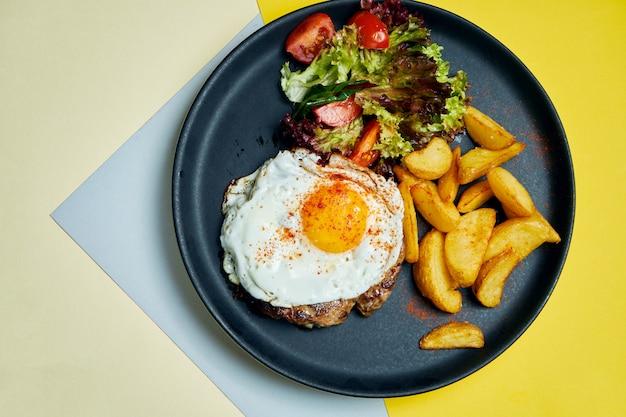 Rindersteak mit spiegeleiern mit einer beilage aus salat und bratkartoffeln auf einem schwarzen teller auf einer farbigen oberfläche appetitliches essen zum mittagessen