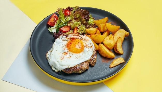 Rindersteak mit spiegeleiern mit einer beilage aus salat und bratkartoffeln auf einem schwarzen teller auf einer farbigen oberfläche. appetitliches essen zum mittagessen