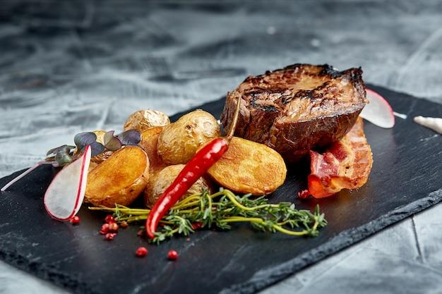 Rindersteak serviert mit ofenkartoffeln und gemüse, schwarze oberfläche, nahaufnahme. konzept essen.