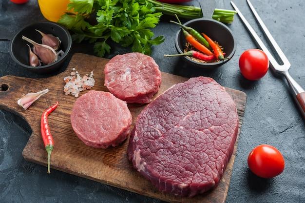 Rindersteaks kochfertig, kulinarischer hintergrund. frisches rohes fleisch auf holzschneidebrett