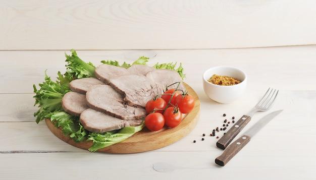 Rinderzunge auf einer platte mit salatblättern, kirschtomaten und dijonsenf
