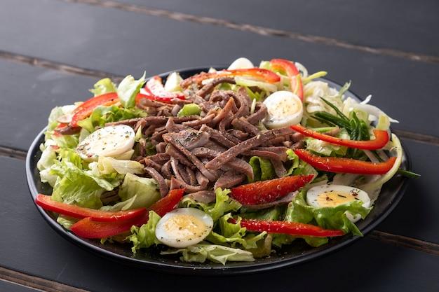 Rinderzungensalat mit frischem gemüse auf einem teller.