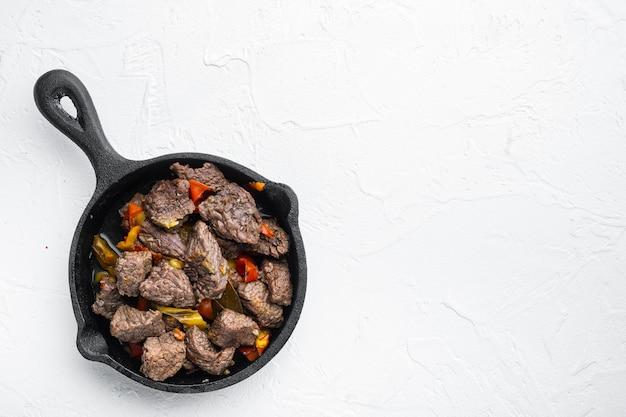 Rindfleisch-bourguignon-eintopf mit gemüse in gusseiserner pfanne auf weißem stein, draufsicht flach gelegt