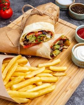 Rindfleisch-burrito mit tomaten-gurken-salat-jalapeno, serviert mit pommes frites und saucen vertikal