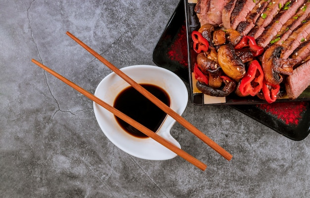 Rindfleisch, champignons und sojasauce mit essstäbchen.