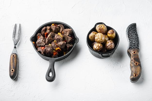 Rindfleisch-eintopf-gulasch - rustikales set in einer gusseisernen pfanne auf einer weißen steinoberfläche