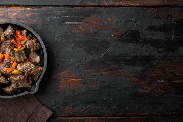 Rindfleisch-eintopf-gulasch - rustikales set, in gusseiserner pfanne, auf altem dunklem holztisch, draufsicht flach gelegt