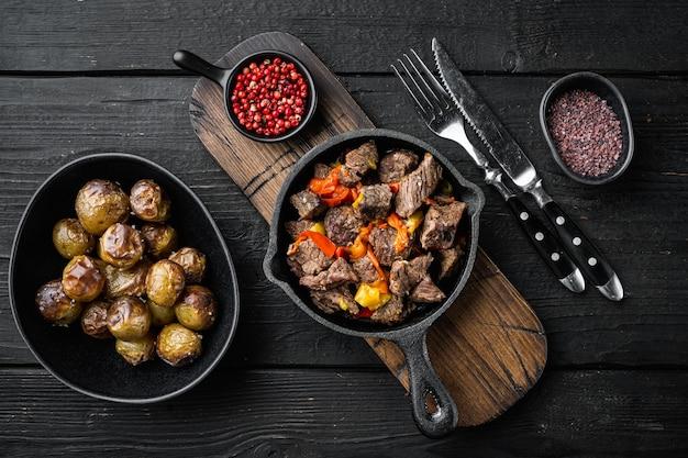 Rindfleisch-eintopf-gulasch - rustikales set, in gusseiserner pfanne, auf schwarzem holztisch, draufsicht flach gelegt