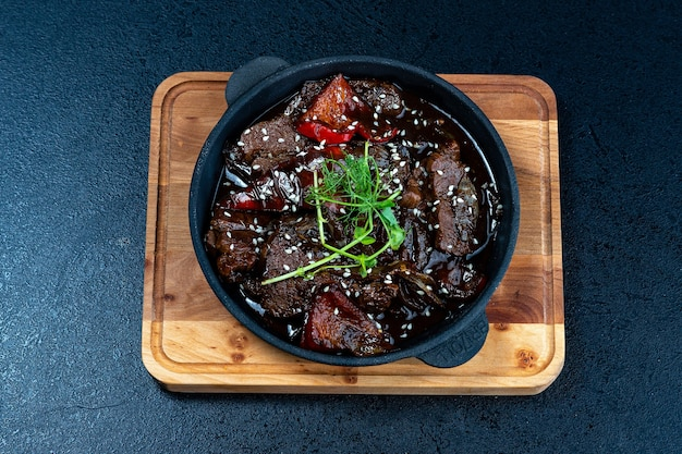 Rindfleisch fleisch und gemüse eintopf in schwarzer schüssel.
