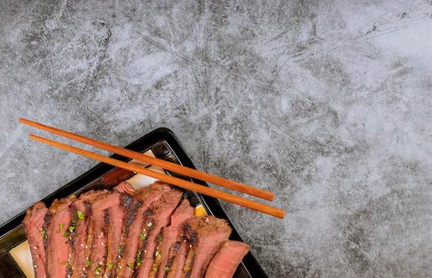 Rindfleisch geschnitten mit essstäbchen auf schwarzblech.