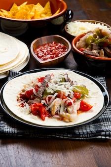 Rindfleisch-hähnchen-fajitas mit buntem paprika in tortillabrot und soßen