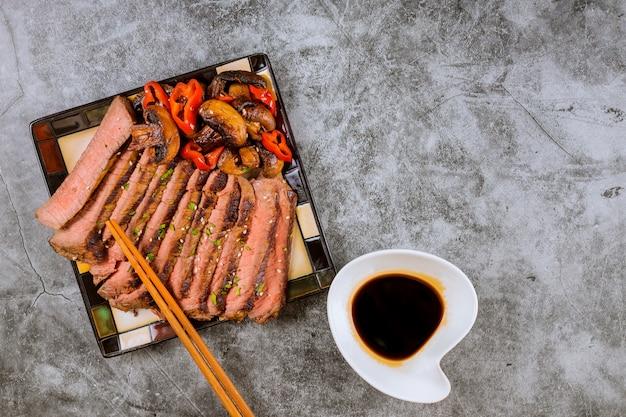 Rindfleisch koreanisches gegrilltes rindfleisch, das dünn vom lendenstück des steaks gemacht wird, briet im roten grünen pfeffer und in den pilzen auf platte mit essstäbchen