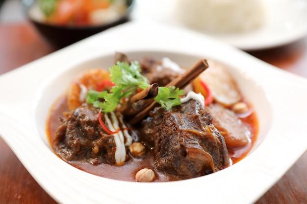 Rindfleisch-massaman-curry mit reis und salat auf hölzernem hintergrund, thailändisches essen
