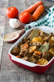 Rindfleisch mit kartoffeln, karotten und gewürzen im keramiktopf auf holztisch gedünstet