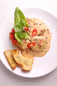 Rindfleisch mit pfeffersoße auf einer weißen platte mit croutons und salatblättern