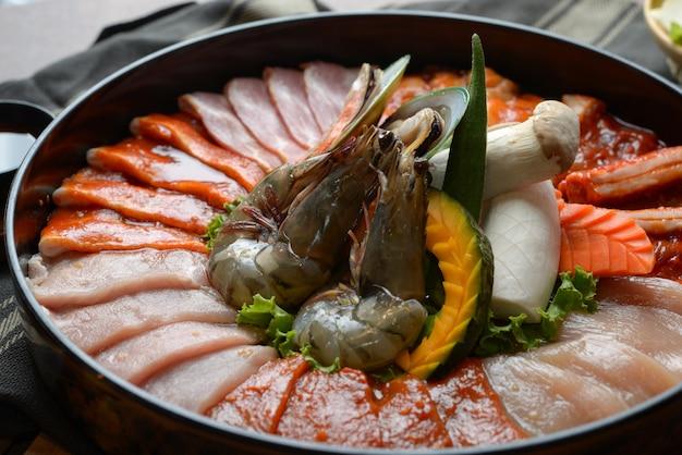 Rindfleisch mit sesam garniert und krustentiere mit krabben auf dem tablett in kombination mit gemüse für den grill auf dem tisch.