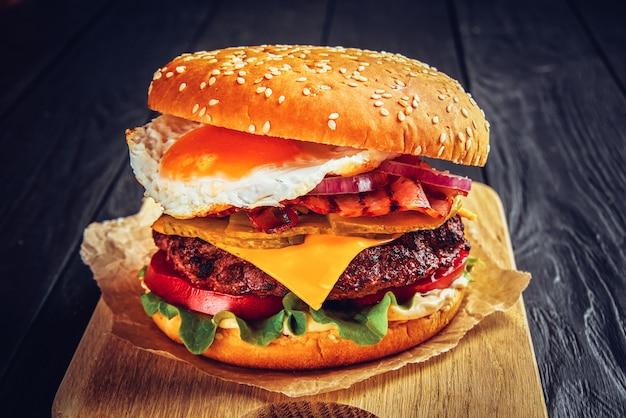 Rindfleischburger mit geschmolzenem käse und speck und ei auf holz