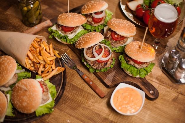 Rindfleischburger mit pommes und ein erfrischendes glas eisbier auf einem restauranttisch. goldenes bier. knoblauch. vintage-restaurant.