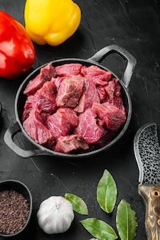Rindfleischeintopf für gulaschkochgarnitur mit süßem paprika in gusseiserner pfanne auf schwarzem steintisch