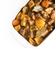 Rindfleischfleisch gedünstet mit kartoffeln, karotten und gewürzen im keramiktopf lokalisiert auf weißem hintergrund draufsicht
