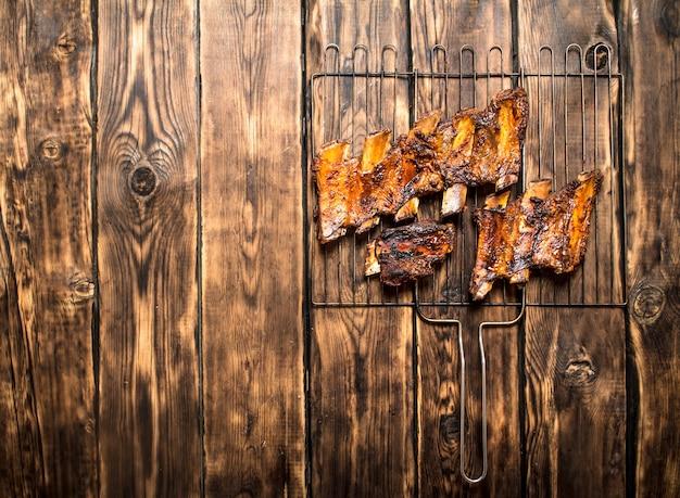 Rindfleischgrillrippen auf grill auf holztisch.