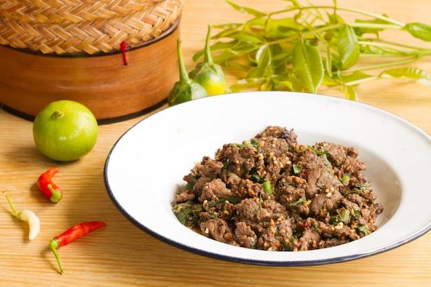 Rindfleischsalat in einer weißen platte auf einem holztisch. , platz für texteingabe