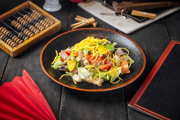 Rindfleischsalat mit gemüse und pilzen auf dem schwarzen holz