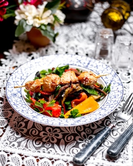 Rindfleischsalat mit paprika-petersilie und olivenöl mit hühnchenstücken am spieß