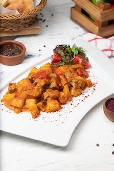 Rindfleischscheiben eintopf in tomatensauce mit zwiebeln und paprika. serviert in weißen teller mit basilikum, schwarzer pfeffer