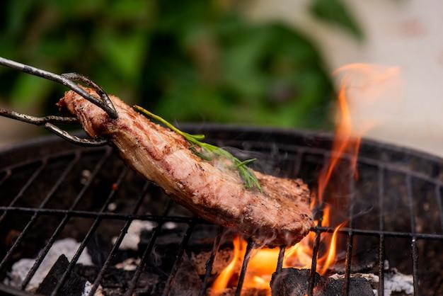 Rindfleischsteak auf dem grillrost, flammen auf hintergrund