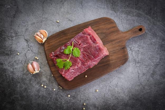 Rindfleischsteak des rohen fleisches mit gewürzknoblauch auf hölzernem schneidebrett und schwarzem hintergrund